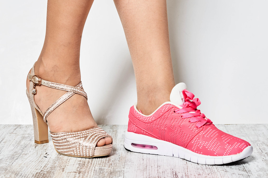 Young beautiful woman makes the choice between comfortable and uncomfortable shoes