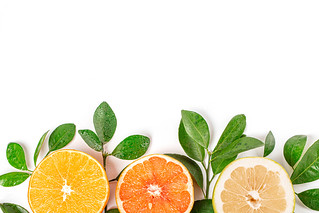 Halves of fresh citrus fruits with branches and green leaves, top view | by wuestenigel