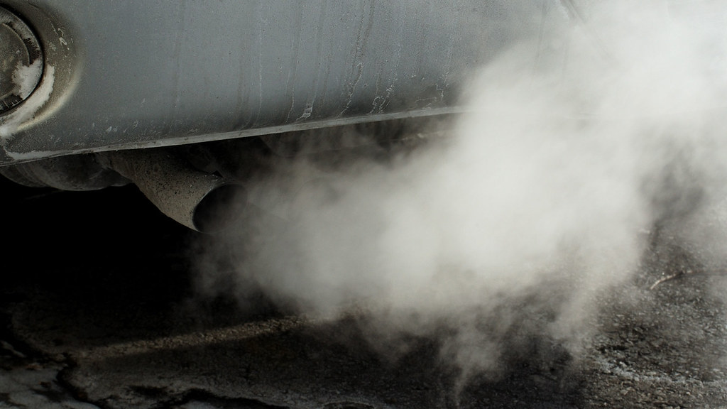 A photo of the exhaust of a car with fumes coming out.