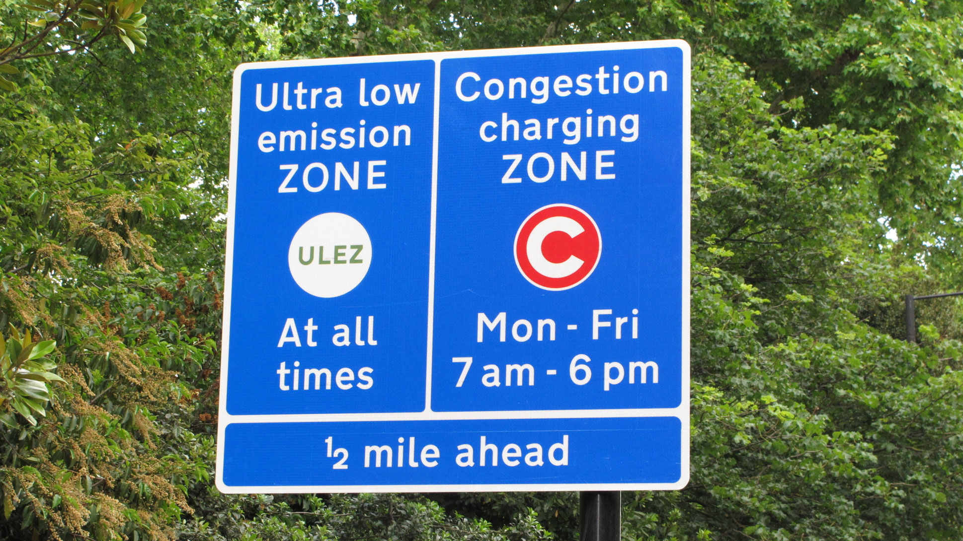 A road sign in blue with the text 'Ultra low emission zone' and 'Congestion charging zone' displayed in it.