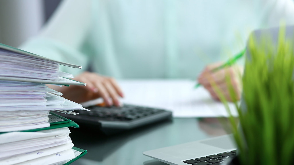 An accountant working with a paper and calculator with a plant and pile of paperwork in the foreground