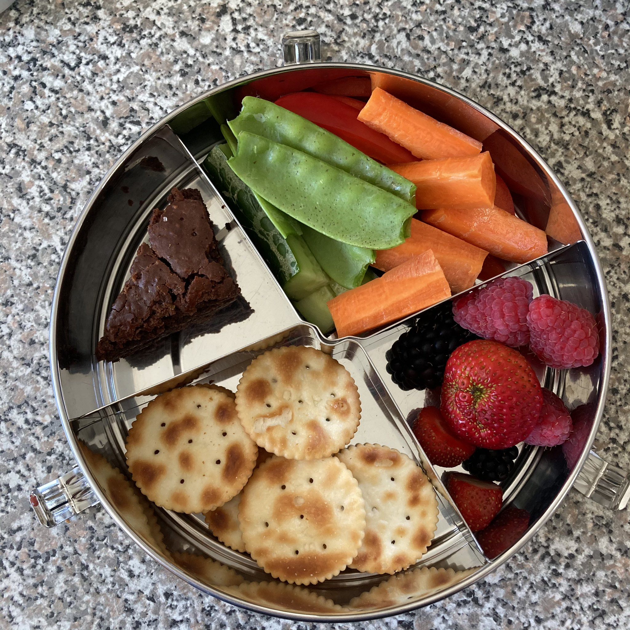 a round stainless steel lunchbox, packed with round crackers, a triangular piece of chocolate brownie, sticks of cucumber, capsicum, carrot and snowpeas and raspberries, blackberries and strawberries