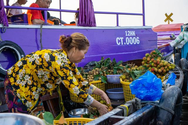 Vietnamesische Frau verkauft frische Longan und Rambutan Früchte auf dem Cai Rang Floating Market in Can Tho, Vietnam