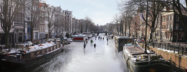 Ice skaters glide over frozen and Historic Prinsengracht in Amsterdam