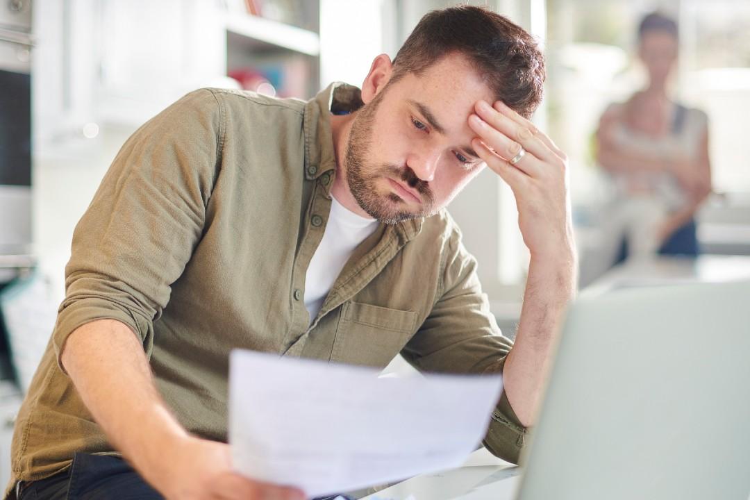 Man looking at paperwork, looking stressed.