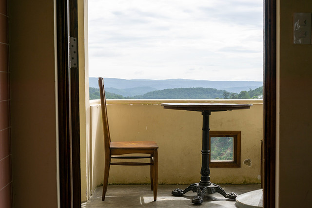 Wooden Table and Chair on a Balcony with Scenic Mountain View in the Background at Dreamers Home and Coffee in Dalat, Vietnam