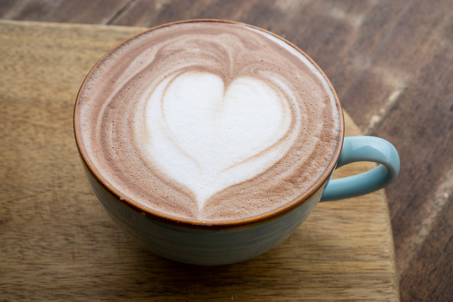 Close Up Photo of Hot Cappuccino Coffee in a Ceramic Mug with Latte Art Heart on a Wooden Background