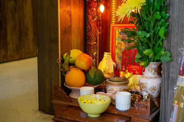 Worship Altar in a Cafe in Vietnam with Fruits, Incense, Liquor, Flowers and other Offerrngs to wish for Good Business