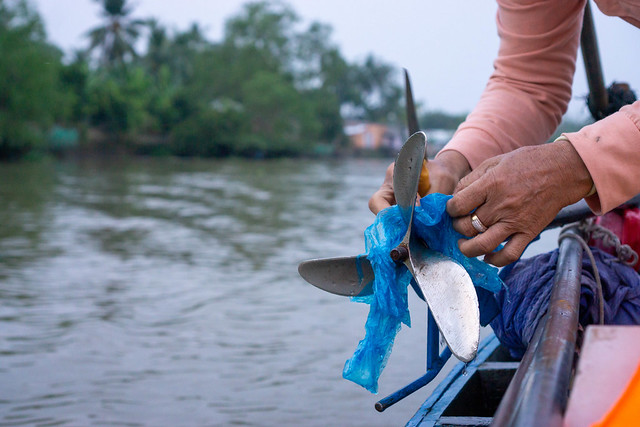 Close Up Photo of a Woman removing a Plastic Bag stuck in a Boat Propeller with a Knife and her Hands