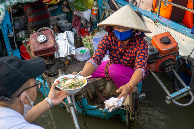 Vietnamese Woman delivering a Bowl of Hu Tieu Noodle Soup from a Boat Restaurant to another Boat at Cai Rang Floating Market in Can Tho, Vietnam
