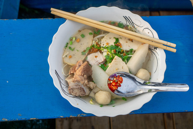 Vietnamese Noodle Soup Hu Tieu with Meatballs, Pork Ham, Pork Meat, Vegetables and Chili in a Bowl with Chopsticks and Spoon on a Boat at Cai Rang Floating Market in Can Tho, Vietnam