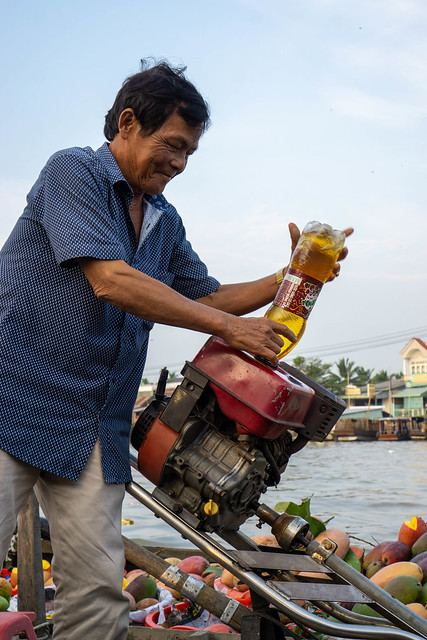 Vietnamese Man fueling an Engine of a Motorboat with Gasoline from Water Bottle at Cai Rang Floating Market in Can Tho, Vietnam