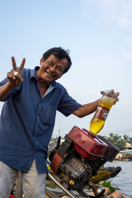 Freundlicher Mann tankt sein Motorboot mit Benzin aus einer Plastikflasche und lacht in die Kamera auf dem Cai Rang Schwimmenden Markt in Can Tho, Vietnam
