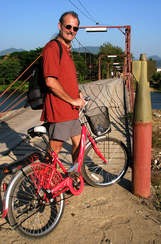 Bicycling across a bridge with 'decorative' recycled bombs in Vang Viene, Laos