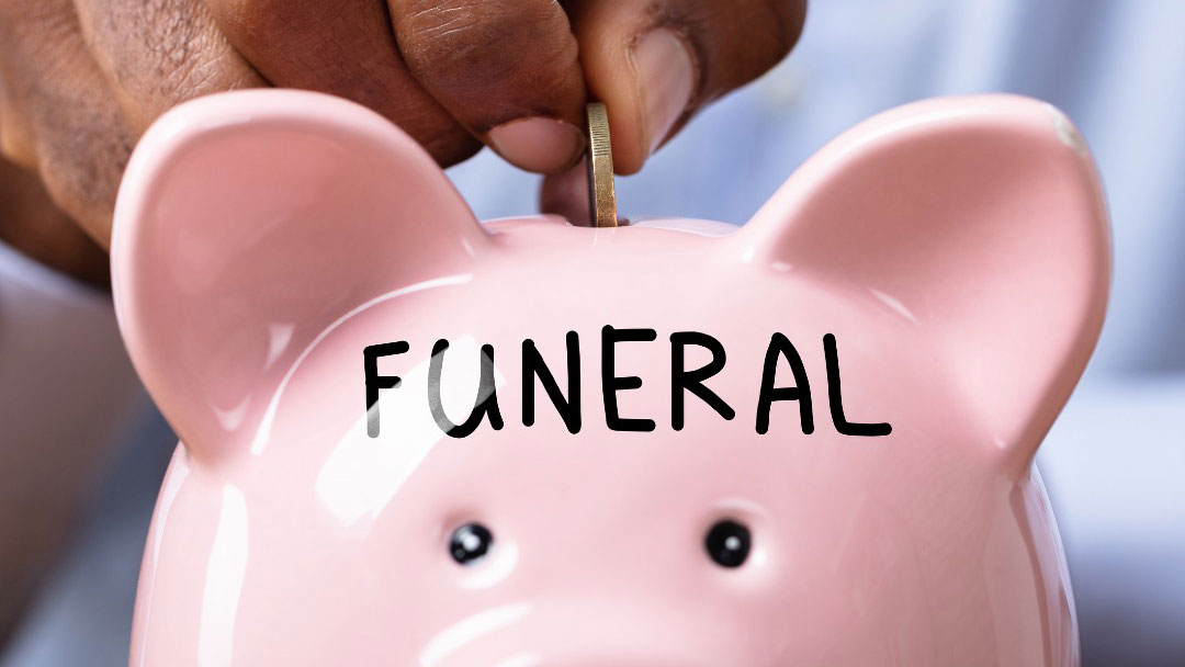 Coin being added to piggy bank labelled 'Funeral'