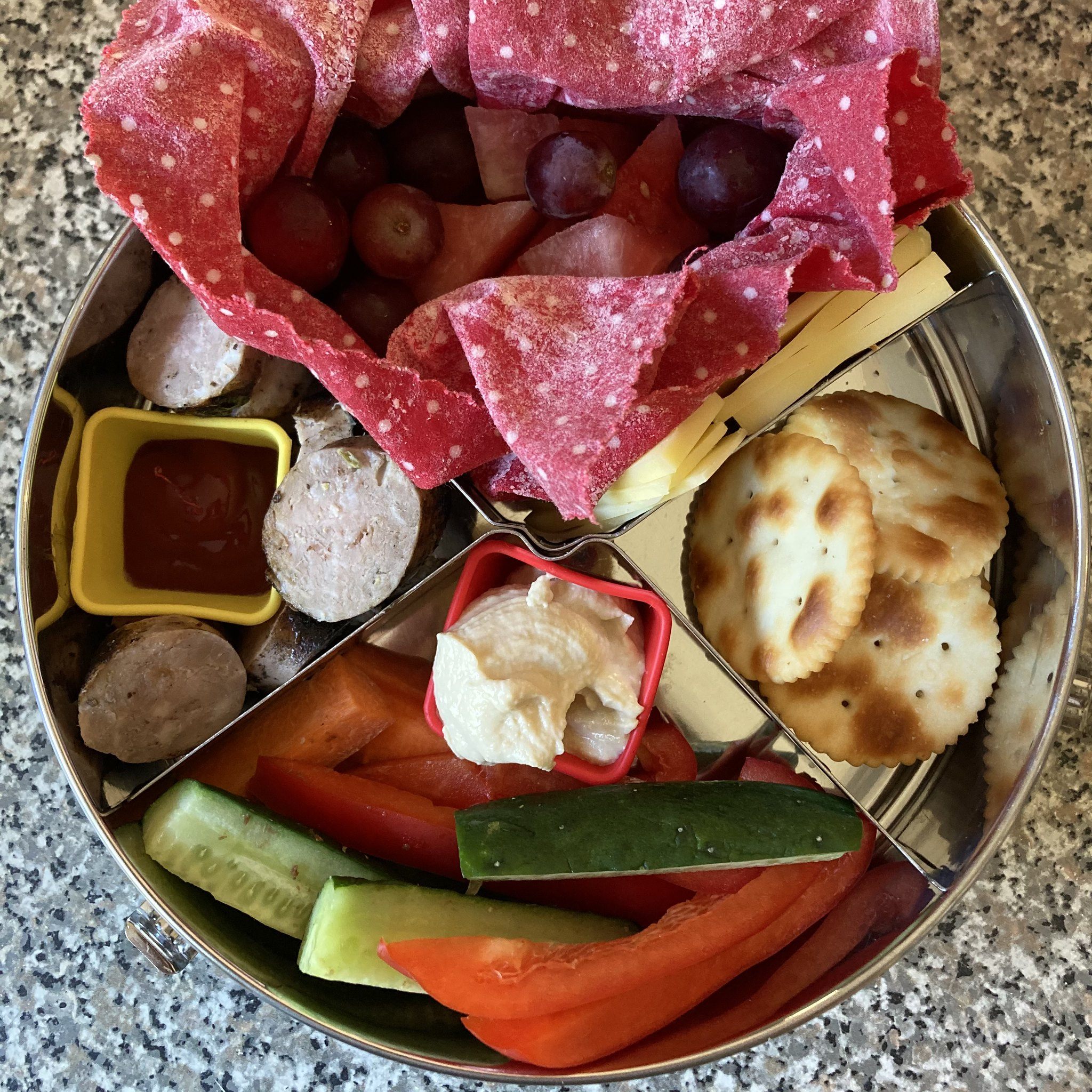 a round stainless steel lunchbox, packed with crackers and cheese, watermelon and red grapes wrapped in a red beeswax wrap, sticks of cucumber, capsicum, carrot and snowpeas with some hommus in a square red silicon container and a sliced up sausage with tomato sauce in a yellow square silicon container