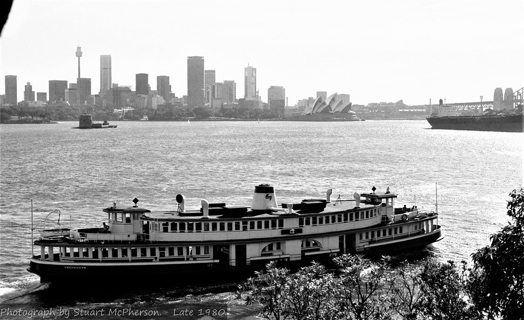 The magnificent, handsome and seriously stylish 1912-built Sydney Harbour ferry Kanangra.  In this image she's doing a Mosman Bay run - and here is pulling into Cremorne Point Wharf with a moderate load of passengers onboard.  A 1980-style Sydney skyline sets the background along with an empty bulk carrier apparently at anchor - a reminder that once upon a time Sydney Harbour was a working port.  This veteran vessel was built locally here in Sydney by Mort's Dock @ Woolwich (near Hunter's Hill) before the First World War, and was one of dozens of her type constructed in this era to cater for Sydney's rapidly expanding public transport needs at that time.  Unlike most of the dozens of 'K Class' ferries of her type (names all began with the letter K), Kanangra's hull was steel and not of wooden construction.  She had a capacity just a bit under 1,000 passengers.  Originally a tall-funnelled coal-burning steam ferry, her boilers and reciprocating steam engine were replaced in the late 1950s with an 8-cylinder Crossley diesel engine - and she continued to operate on Sydney Harbour until the mid-1980s.  Kanangra's working life spanned well over 70 years.  Fortuitously and wonderfully - Kanangra survives to this day at the grand old age of 109 years, and is currently owned and under restoration by the Sydney Heritage Fleet - located in Sydney Harbour's Rozelle Bay.  It is intended that she ultimately be restored to full operating condition, and that we will one day again see this rare and truly magnificent vessel gracing Sydney Harbour.  Stuart McPherson photo.  Late 1980.