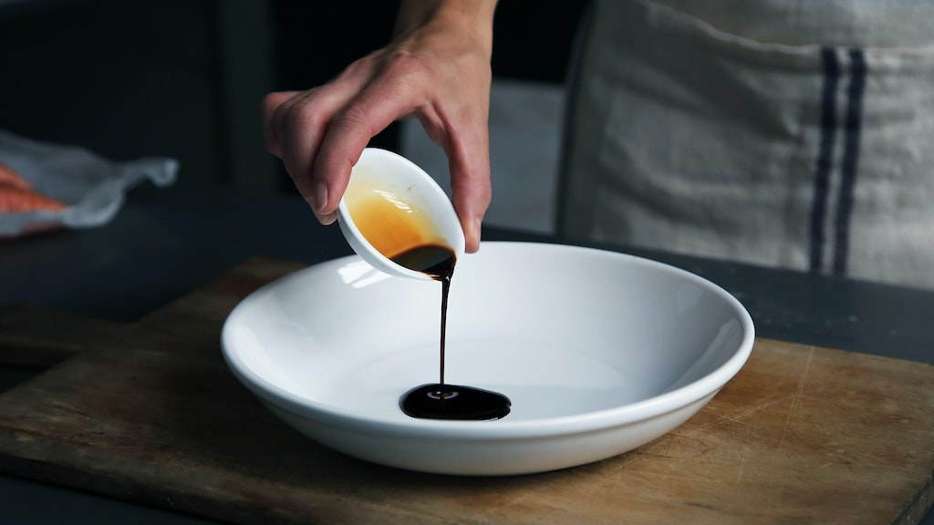 Dark soy sauce being poured into a white bowl.