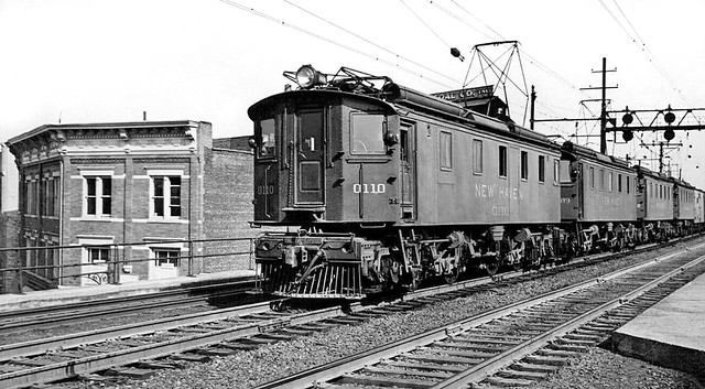 New Haven Railroad with EF-1 motor # 0110, along with three additional motors, are seen leading a manifest freight train on an elevated portion of the electrified main line in Connecticut, ca 1940's