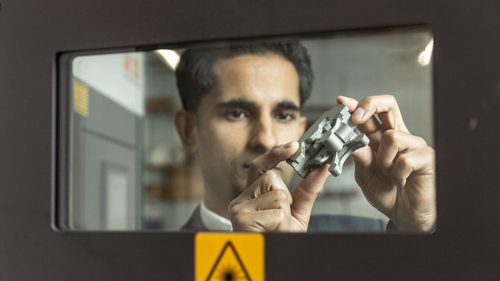 Vimal examines an additively manufactured servovalve behind the door of an AM machine.