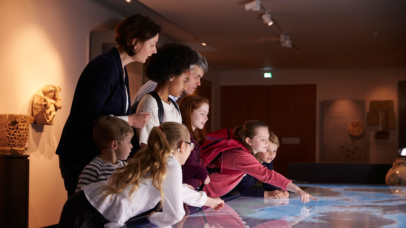 Some adults with a group of children in a museum. The children are leaning over and pointing at a large map.