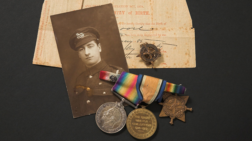 A photo of a selection of memorabilia including a photo of a soldier, some medals and birth certificate