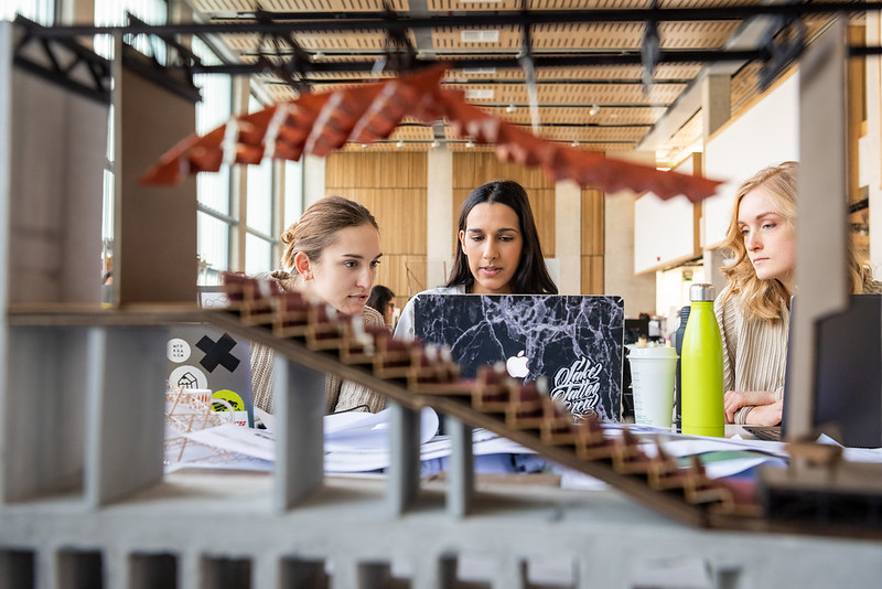 3 architecture female students  sat in front of a cardboard model of a building which is in he foreground. The students are in the background.