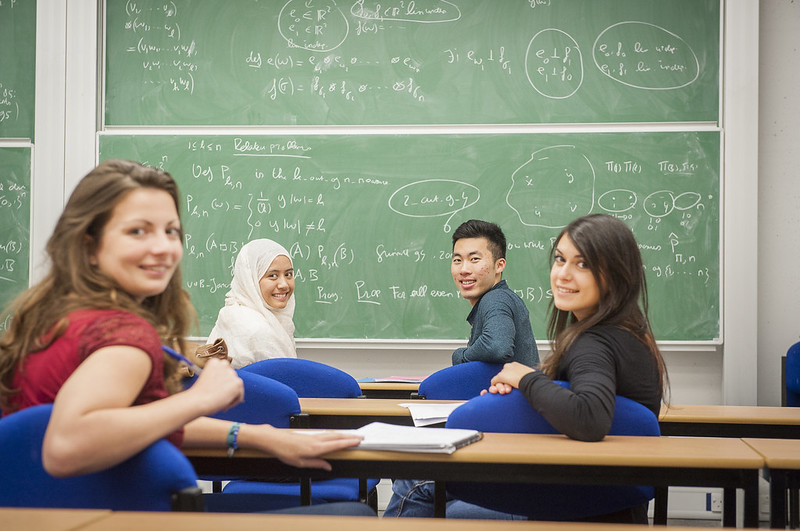 3 female and 1 male student turning their backs to face the camera sat in front of a green chalk board covered in mathematical equations