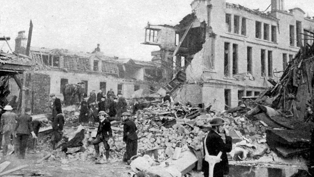 An old photo of rescue workers searching through wreckage after a bombing.