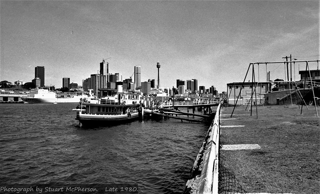 The 1913-built wooden-hulled Sydney Harbour ferry Lady Edeline calls in at Darling St (Balmain) Wharf during the latter part of the year 1980.  Lady Edeline was built locally here in Sydney by G A Washington's yard in Balmain before the First World War for the Balmain New Ferry Company.  Originally a coal-burning steam ferry that was later converted to diesel propulsion, she was employed at first around the Balmain Peninsula and Lane Cove River until the smaller company was later taken over by its larger corporate rival Sydney Ferries Ltd.  This veteran vessel would go on to have a career of over seven decades and continued to work regularly on Sydney Harbour as late as 1984.    One of the last of the large all-wooden Sydney ferries in service on the Harbour, she would finally be retired (along with the remaining others) soon after the January 1984 sinking of the ferry Karrabee at Circular Quay the day of the Sydney ferry boat race that year.  Remaining moored at various locations on the Harbour for a few years thereafter, she sadly ended her days in 1988 sinking into the mud near Mortlake Point on the Parramatta River.  The remains of her hull can still be seen at low tide near the South side of the Mortlake / Putney punt.  Stuart McPherson photo.  Balmain NSW,  late 1980.