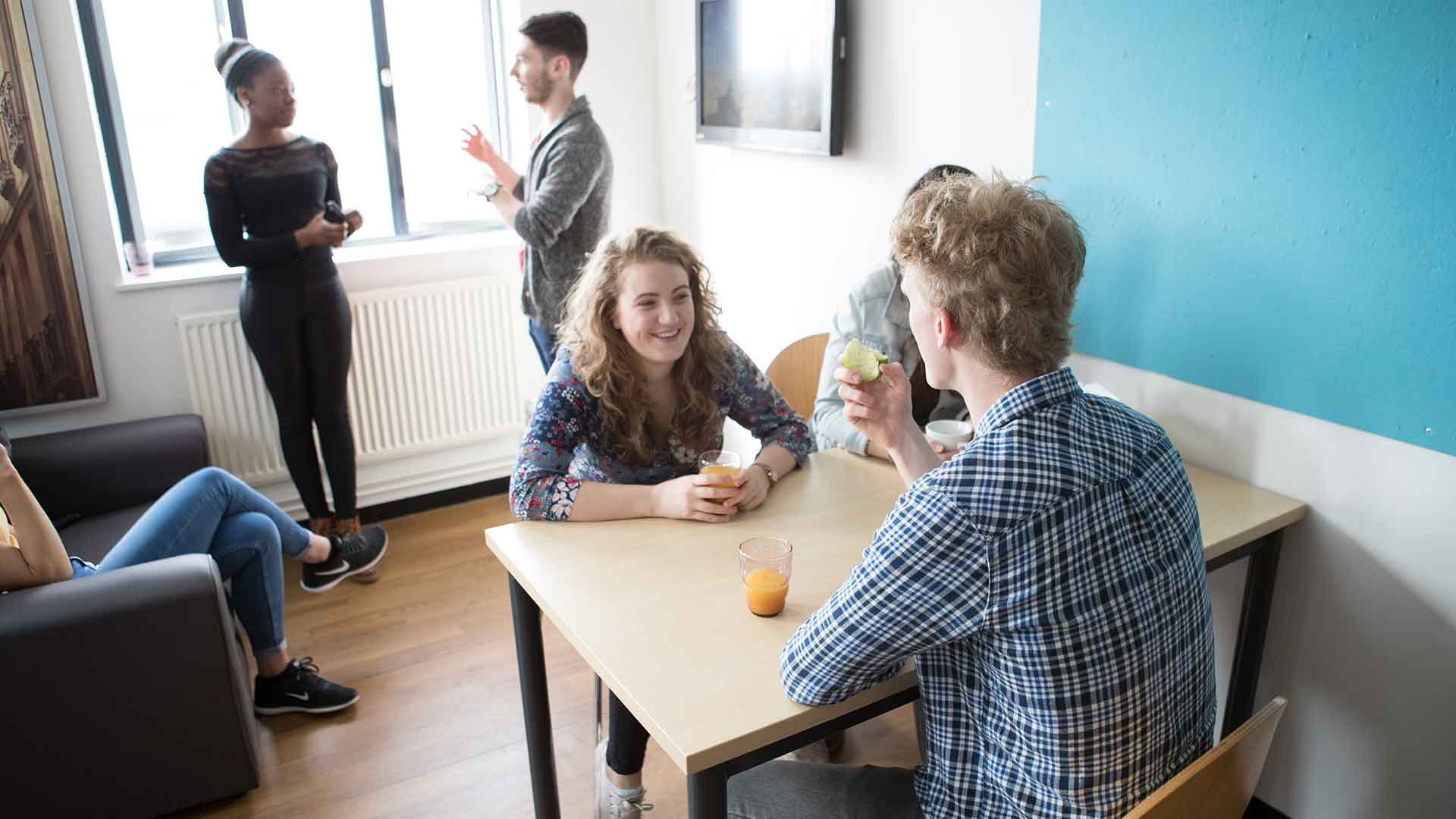 Students chatting in a kitchen.
