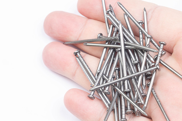 Pile of Nails in the hand above white background