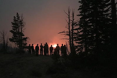 A crew of firefighters and conifer trees are silhouetted on a ridgetop by a wildfire burning brightly in the distance after or near sundown.