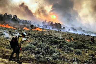 Firefighter walks along a road checking for spot fires in a meadow filled with sagebrush. active fire is burning in the distance and smoke rises in the background, obscuring a  setting sun. A helicopter can   be seen flying in the smoke.