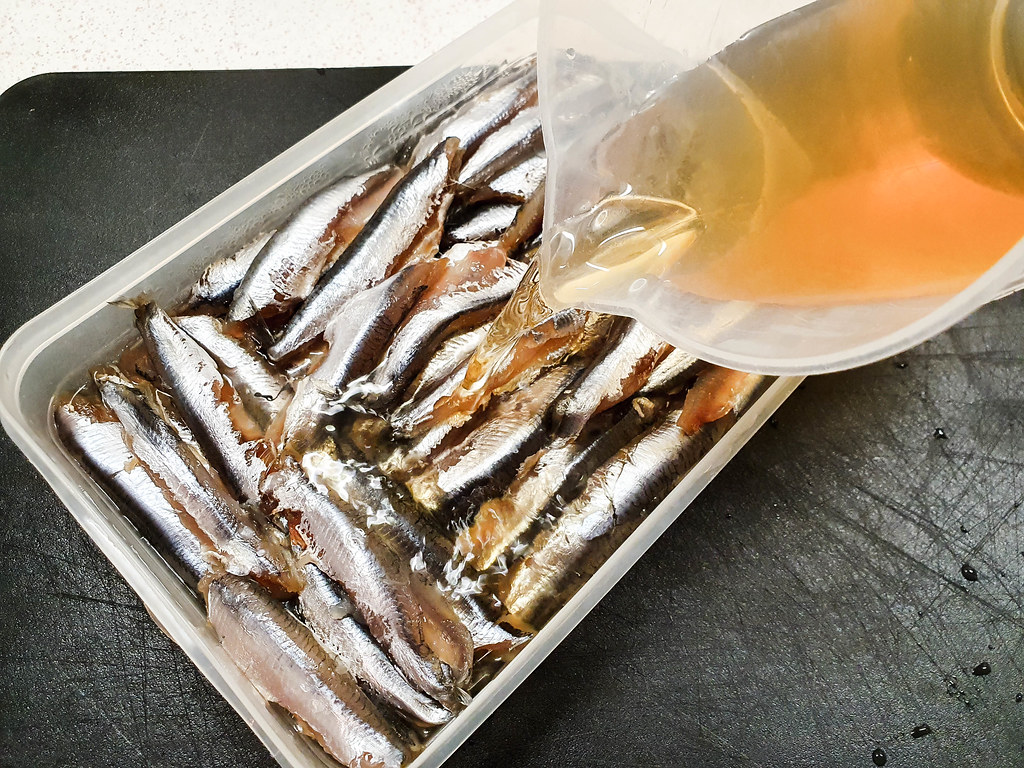 the fish arranged one on top of the other in a rectangular Tupperware. A yellowish vinegar mixture is poured on top of them from a plastic jug
