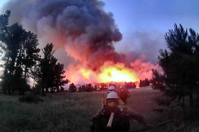 A single-file line of firefighters walks through a meadow carrying their line tools  toward an actively burning fire putting up a heavy column of smoke.