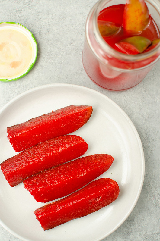Plate of 4 cherry Kool Aid Pickles with jar of red pickles