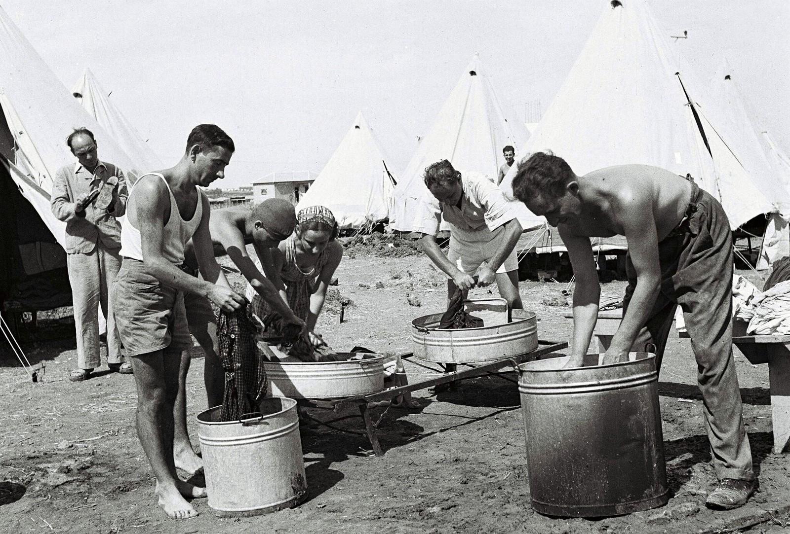 11. Новые еврейские иммигранты стирают свою одежду в своем палаточном лагере 1 марта в кибуце Наан