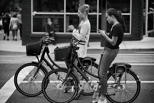 ian sane images atthelight women bicycles waiting cellphones viewing intersection southwest 10th avenue burnside downtown portland oregon monochrome blackwhite candid street photography canon eos 5ds r camera ef70200mm f28l is usm lens monochromemonday