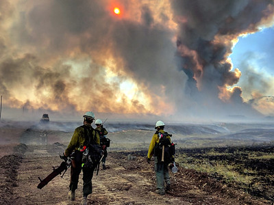 three firefighters in wildland gear walk away from the camera in a dozer line with dark wildfire smoke in the background obscuring the sun and sky.