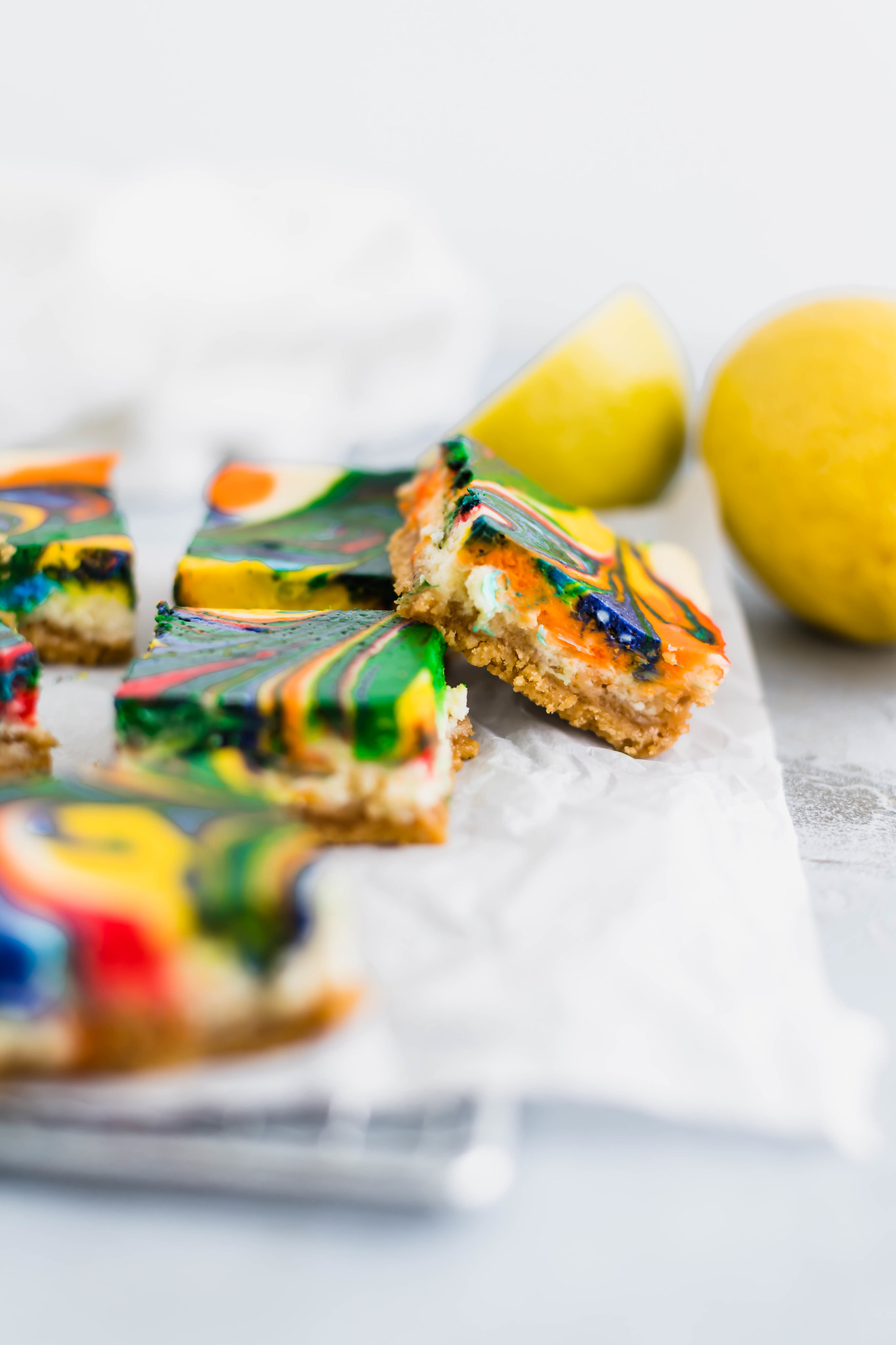 Celebrate St. Patrick's Day with these adorable, incredibly delicious Rainbow Lemon Cheesecake Bars. A lemon oreo crust is topped with a simple lemon cheesecake filling then swirled with all the colors of the rainbow. Switch up the colors of these cheesecake bars to make them for any occasion.