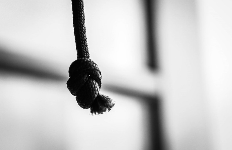 A black and white image of a knotted rope hanging
