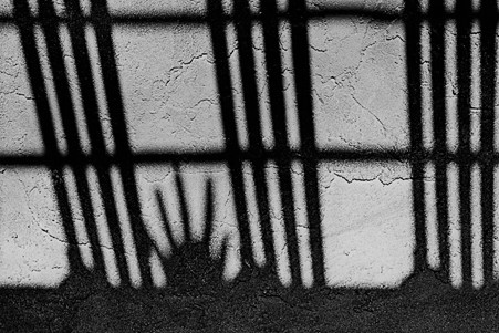 A black and white image showing the shadow of a hand behind bars