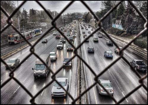 crazytuesday frozenintime commutertraffic cars train freeway fence chainlink rain wetpavement viewfromoverpass
