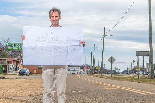 Richard Burt holds design schematics by a roadside in Selma, Alabama.