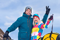 Smiling Caucasian Couple Having Tube Activities In Winter Time In Mountains