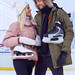 Winter Sports and Lifestyle. Young Caucasian Couple in Winter With Ice Skates Posing Together Over a Snowy Winter Landscape Outdoor.Vertical Image Composition