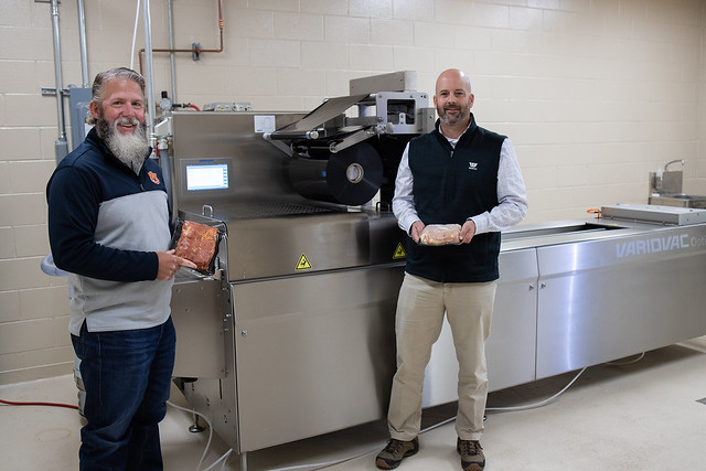 Jason Sawyer, associate professor in Auburn's Department of Animal Sciences, and Tom Bonner, protein market director at Winpak and an Auburn alumnus, display meat products packaged with the VarioVac Rollstock Packaging Machine provided by Winpak