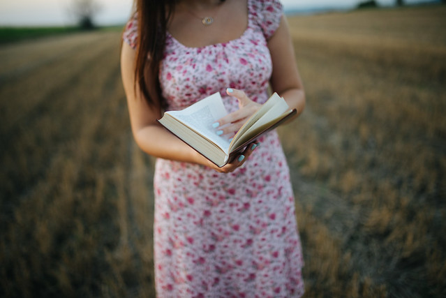Woman holding a book in the field with a blurry background.