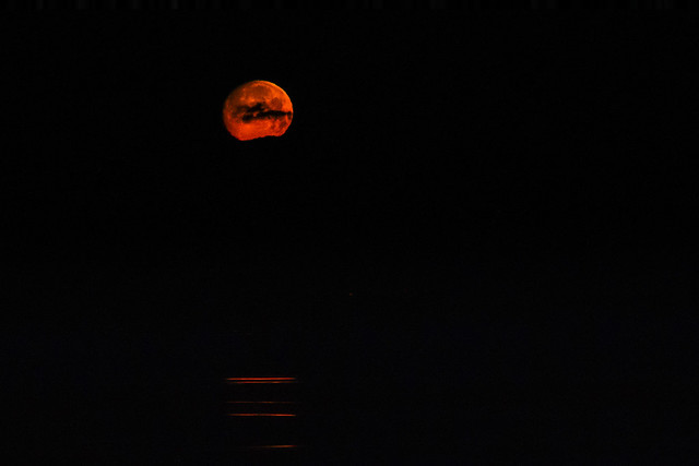 Red Moonset Over Water